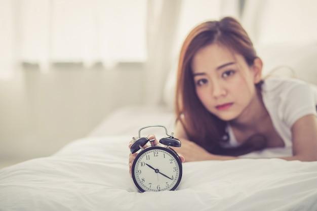 De mooie aziatische vrouw schakelt wekker in goedemorgen uit