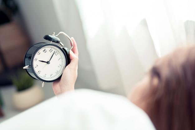 De mooie aziatische vrouw schakelt wekker in ochtend uit.