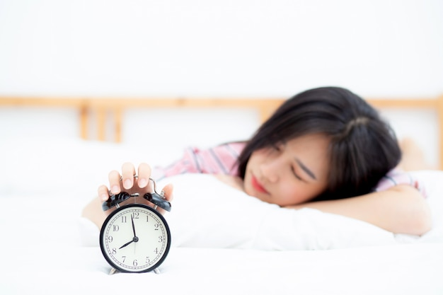 De mooie aziatische vrouw schakelt wekker in ochtend uit