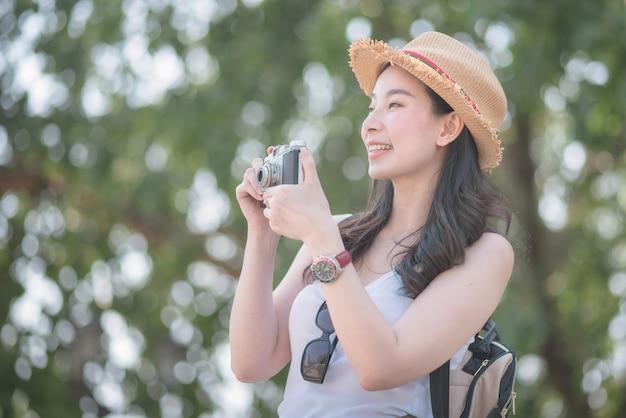 De mooie aziatische vrouw van de solooerist geniet van nemend foto door retro camera bij sightseeingsvlek.