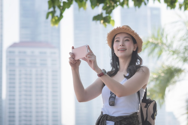 De mooie aziatische vrouw van de solooerist geniet van nemend foto door slimme telefoon bij sightseeingsvlek.