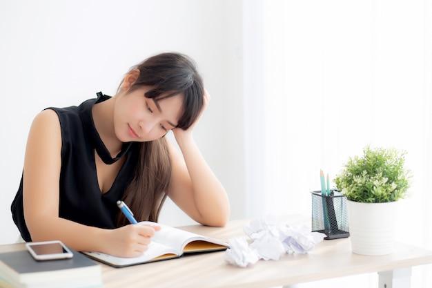 De mooie aziatische vrouw vermoeide en beklemtoond met schrijven overwerkt bij bureau