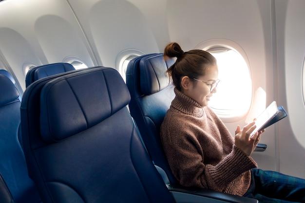 De mooie aziatische vrouw werkt met tabletcomputer in vliegtuig
