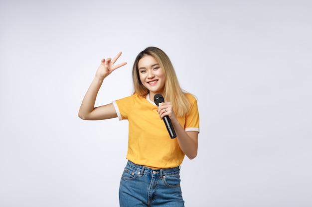 De mooie aziatische vrouw zingt een lied aan microfoon