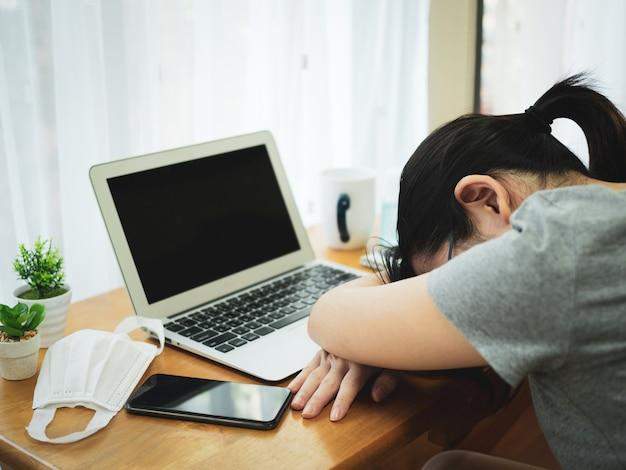 De mooie aziatische vrouwen werken thuis gebruikend notitieboekje en het vermoeide slapen na ontmoeting met team om verspreiding van coronavirus te verminderen.
