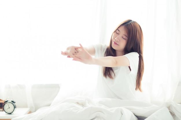 De mooie aziatische vrouwenrek en ontspant in bed
