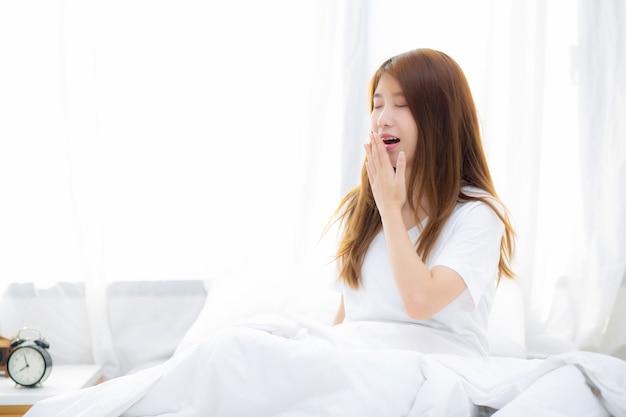 De mooie aziatische zitting van de vrouwengeeuw met slaap op bed