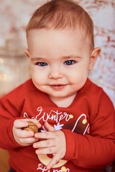 De mooie baby met blauwe ogen houdt een noot vast
