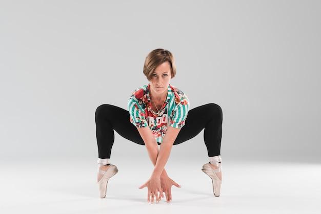 De mooie ballerina danst op de uiteinden van de tenen op grijze achtergrond