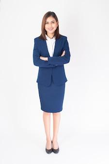 De mooie bedrijfsvrouw in blauw kostuum glimlacht op witte achtergrond