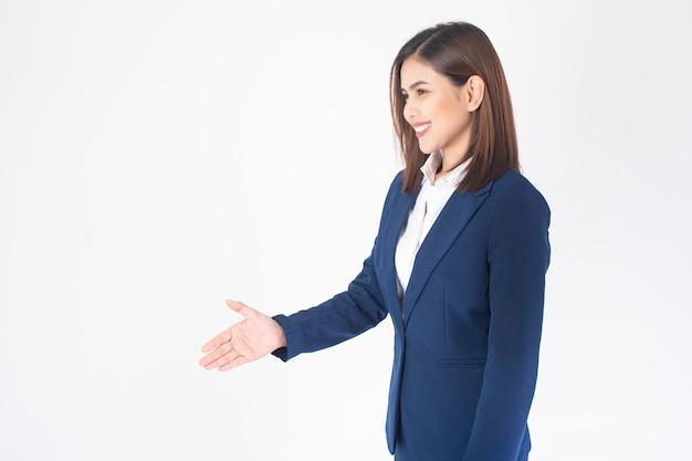De mooie bedrijfsvrouw in blauw kostuum schudt hand op witte achtergrond