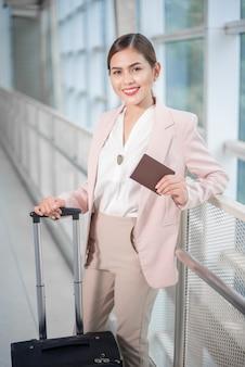 De mooie bedrijfsvrouw loopt in luchthaven, bedrijfsreisconcept