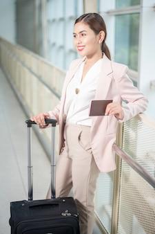 De mooie bedrijfsvrouw loopt in luchthaven