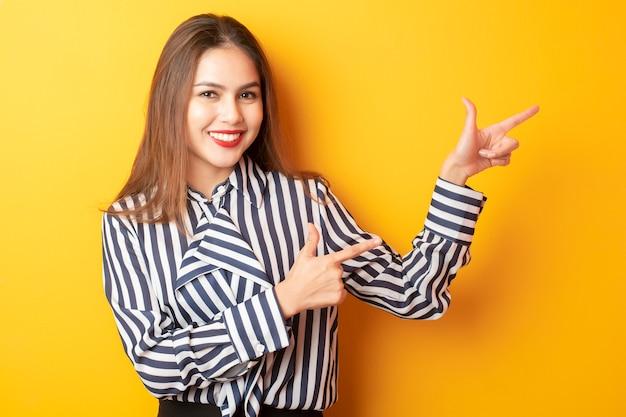 De mooie bedrijfsvrouw stelt iets op gele achtergrond voor
