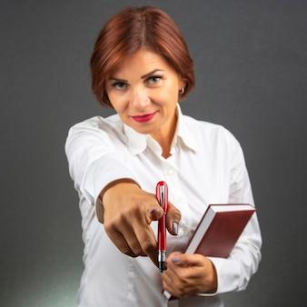 De mooie bedrijfsvrouw strekt zich voorwaartse hand met rode pen uit