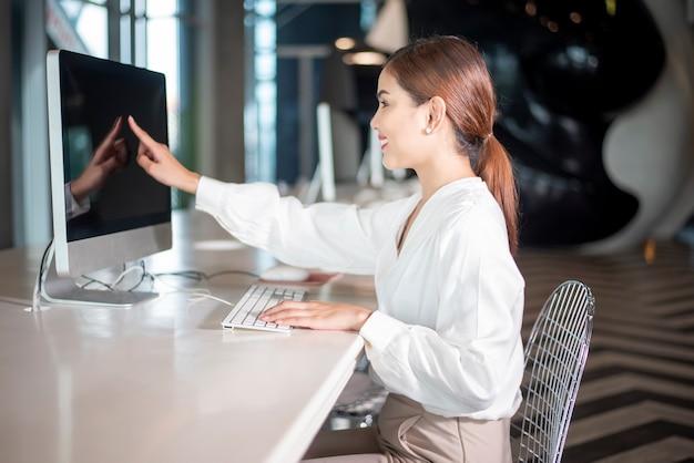 De mooie bedrijfsvrouw werkt met haar computer
