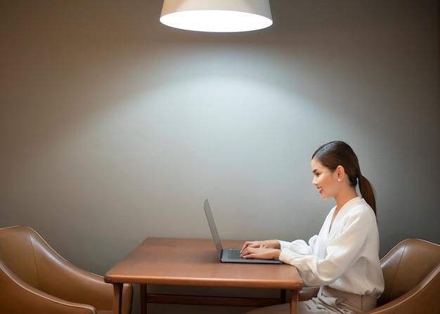 De mooie bedrijfsvrouw werkt met laptop in koffie