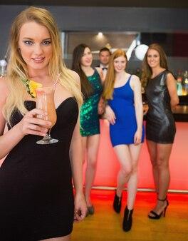 De mooie blonde cocktail die van de vrouwenholding zich voor haar vrienden bevindt