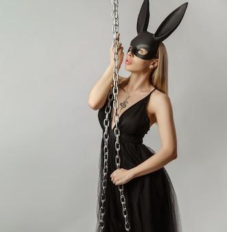 De mooie blonde in een konijnenmasker in een sexy avondjurk op een witte achtergrond met een metalen ketting
