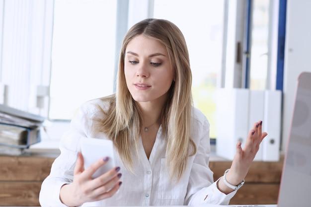 De mooie blonde nadenkende onderneemster bekijkt in hand portret van cellphone.