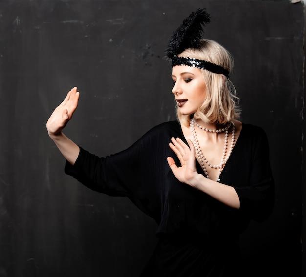 De mooie blondevrouw in jaren '20 kleedt het dansen op donkere achtergrond
