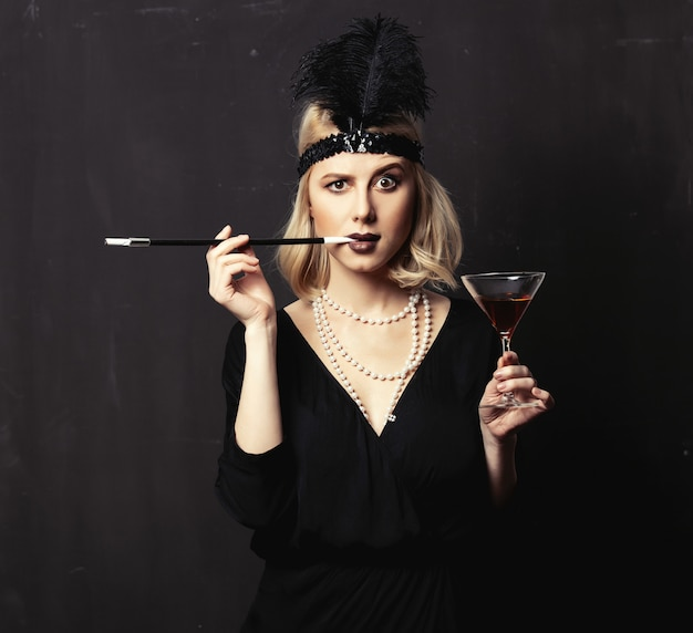 De mooie blondevrouw in jaren 20 kleedt zich met rokende pijp en cocktail op donkere achtergrond