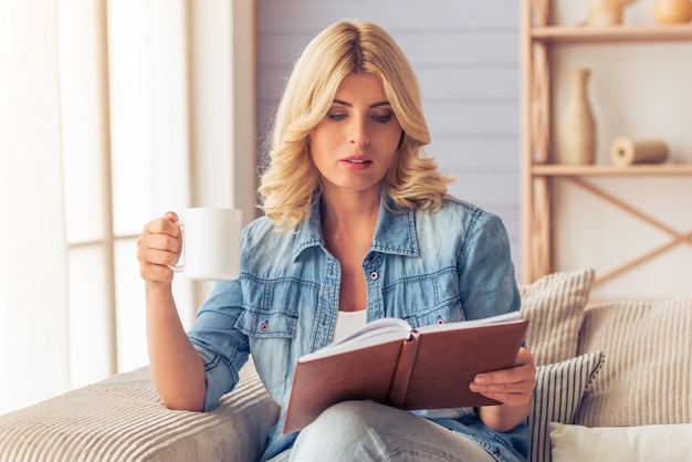 De mooie blondevrouw in jeansoverhemd leest een boek.