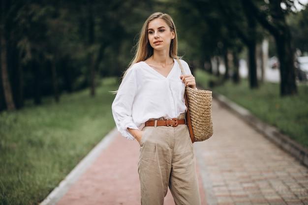De mooie blondevrouw in park die de zomer draagt ziet eruit