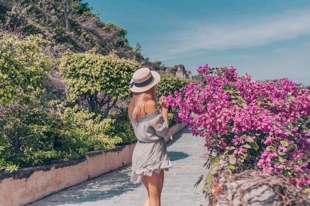 De mooie blondevrouw loopt en bewondert tropische landschappen bij het hotel van het paradijseiland in sanya, china.
