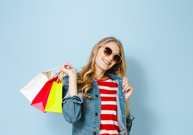 De mooie blondevrouw met zonnebril geniet van winkelend op de blauwe achtergrond