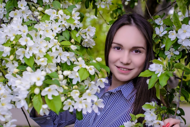 De mooie bomen van de meisjes dichtbij bloeiende appel in de lente
