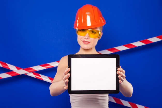 De mooie bouwersvrouw in wit overhemd, bouwersriem, helm, bouwersglazen, jeansborrels en giechels houdt lege tablet