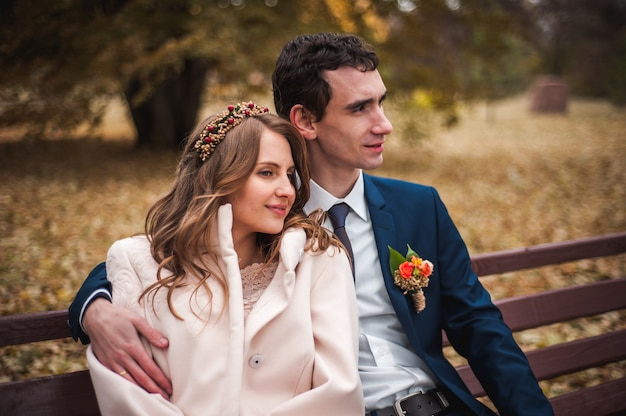 De mooie bruid en knappe bruidegom zittend op een bankje