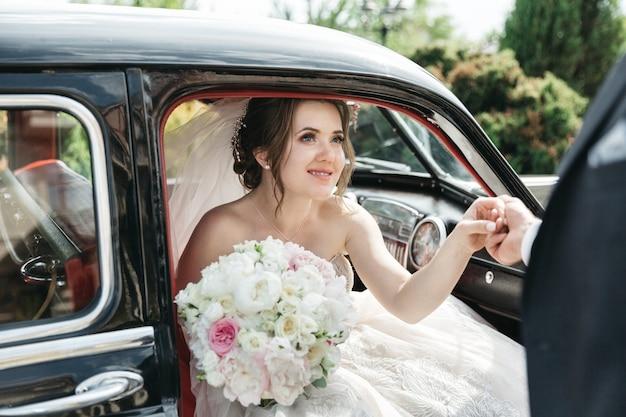 De mooie bruid komt uit de auto