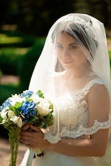 De mooie bruid met huwelijk bloeit boeket, aantrekkelijke vrouw in huwelijkskleding.