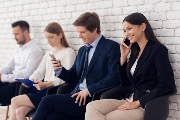 De mooie brunette communiceert op telefoon in wachtkamer