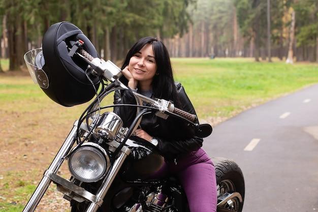 De mooie brunette op een motorfiets