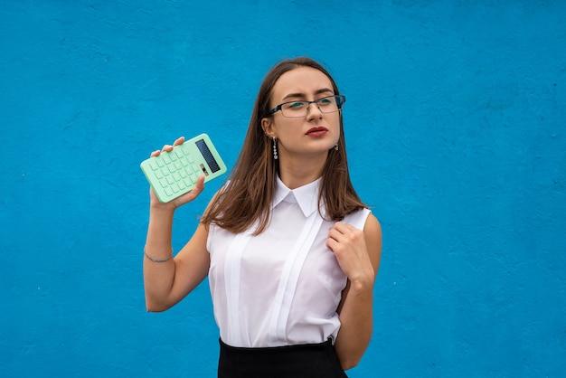 De mooie calculator van de bedrijfsvrouwengreep op blauwe achtergrond