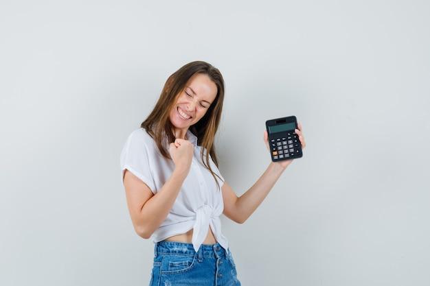 De mooie calculator van de dameholding terwijl het winnaargebaar in witte blouse, jeans wordt getoond en energiek eruit ziet. vooraanzicht.