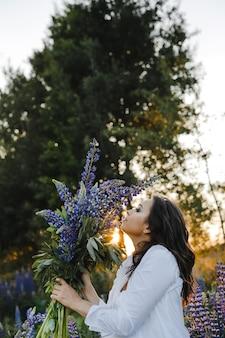 De mooie dame ruikt een boeket van lupines op zonsondergang