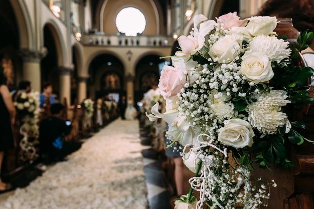 De mooie decoratie van het bloemboeket voor huwelijk in een kerk met onduidelijk beeldachtergrond.