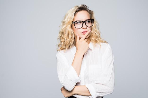 De mooie denkende blonde bedrijfsvrouw isoleerde witte muur