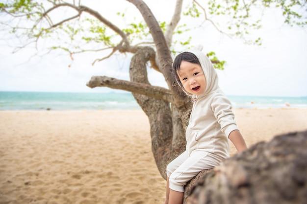 De mooie dochter zit op een boom en genietend van het uitzicht op het strand. familieconcept