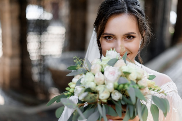 De mooie donkerbruine bruid kijkt recht en houdt huwelijksboeket dichtbij gezicht