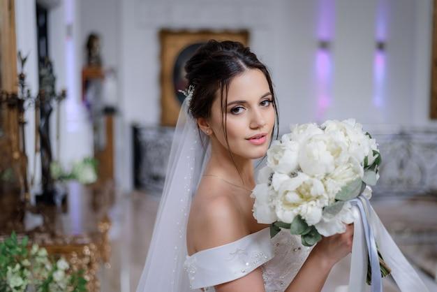 De mooie donkerbruine kaukasische bruid houdt boeket van witte pioenen en kijkt recht binnen