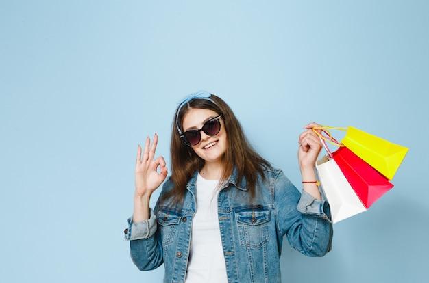 De mooie donkerbruine vrouw met zonnebril geniet van winkelen zij op een blauwe achtergrond heeft gemaakt