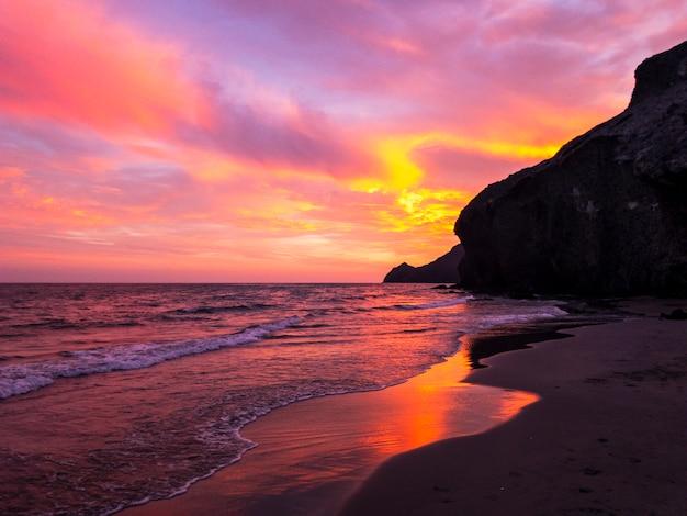 De mooie donkeroranje schoonheid van de hemelavond en wolken bij zonsondergang, dageraad, breken de stralen van de zon door de wolken
