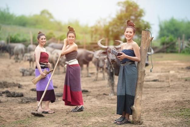 De mooie drie aziatische vrouwen kleedden zich in traditioneel kostuum met buffels bij landbouwgrond, houden vooraan oude radio in hand, houden één messchede en houden schop in hand.
