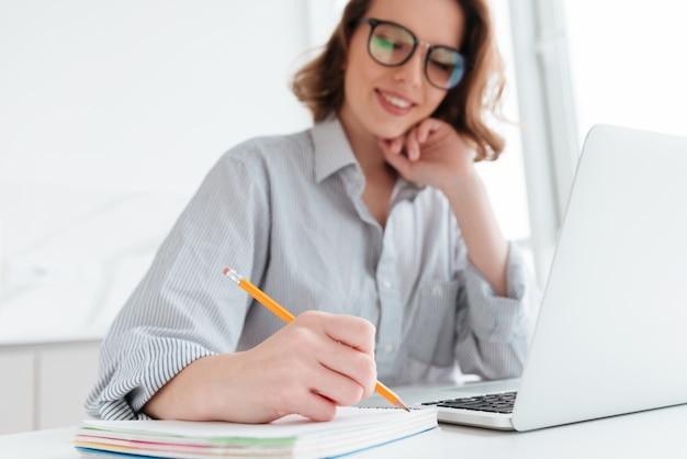 De mooie elegante vrouw in vrijetijdskleding het schrijven neemt nota van terwijl het zitten in lichte keuken, selectieve nadruk op hand