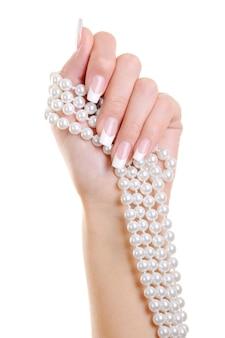 De mooie elegante vrouwenhand met franse manicure houdt de witte perl over